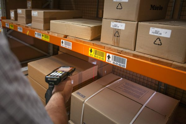 Person scanning warehouse racking label