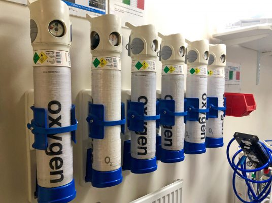 Five oxygen tanks mounted on a wall